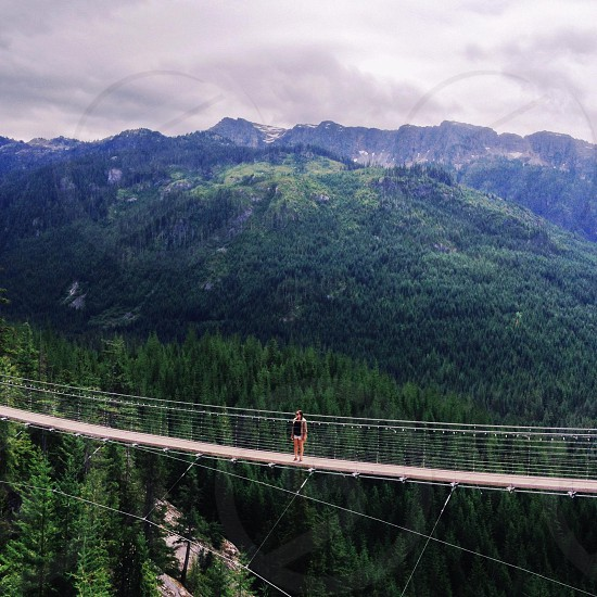woman in white shorts standing in beige hanging bridge photo