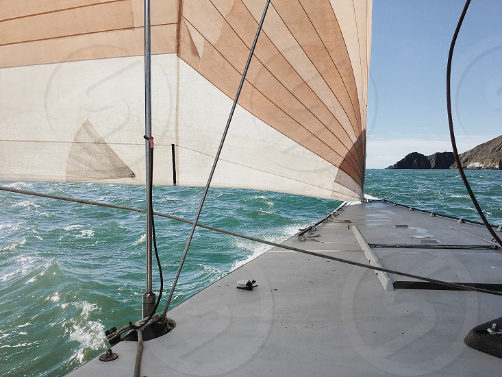 grey and brown sailing boat near sea waves under white and blue sky during daytime photo