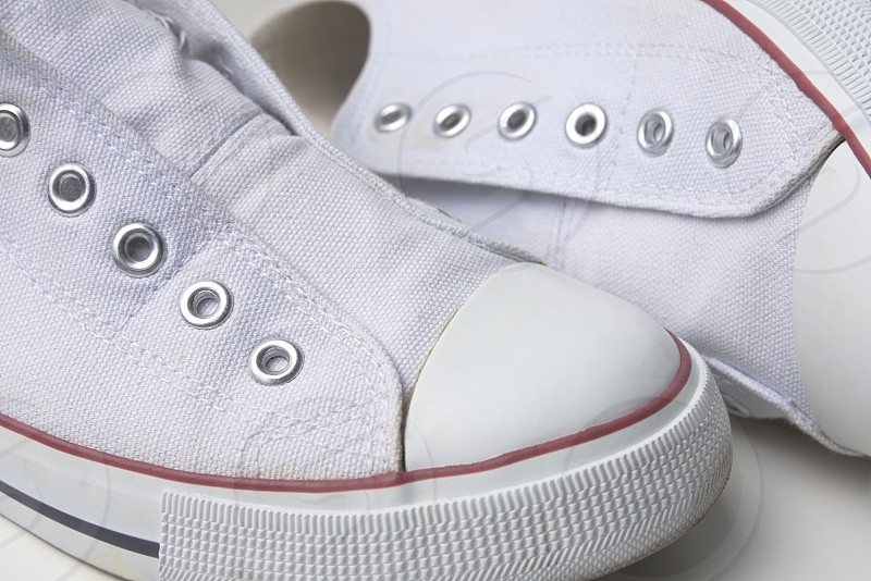 Pair of White Laceless Sneakers with Red Stripe Closeup photo