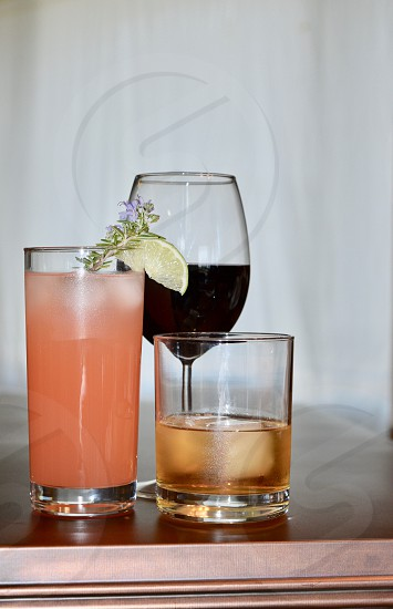 trio of wine whiskey and paloma cocktail in glasses with rosemary and lime garnish photo