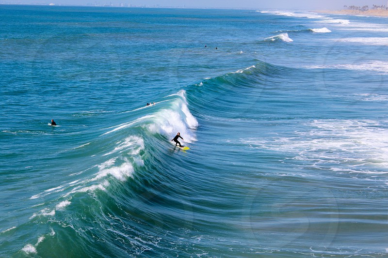 person in wet suit surfing  on green sea wave during daytime photo