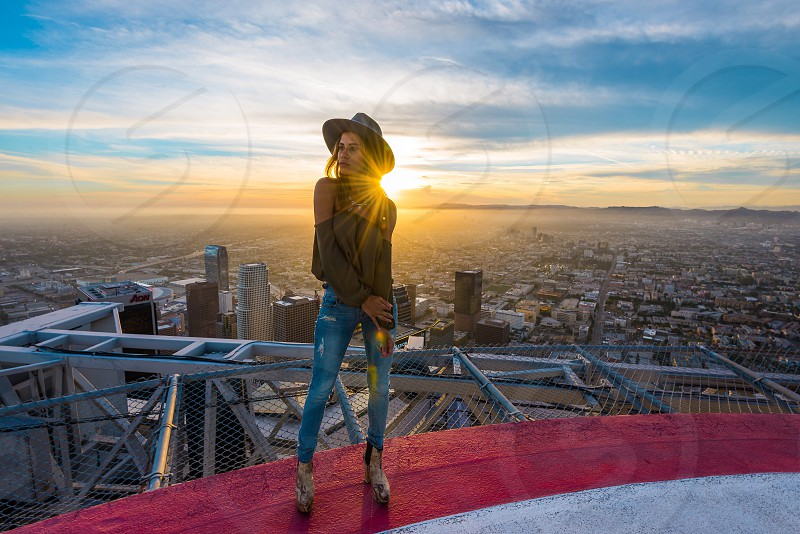 woman in blue denim jeans at rooftop during sunset photo