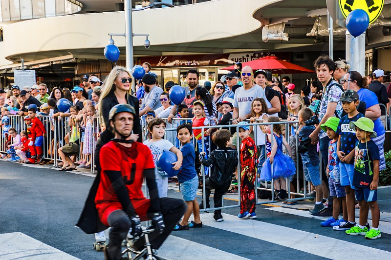 performers entertaining a crowd as they wait for a street parade to begin photo