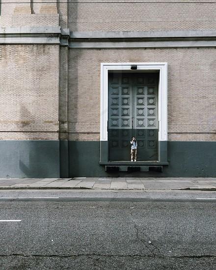 man in brown pants standing in front of grey and green door photo