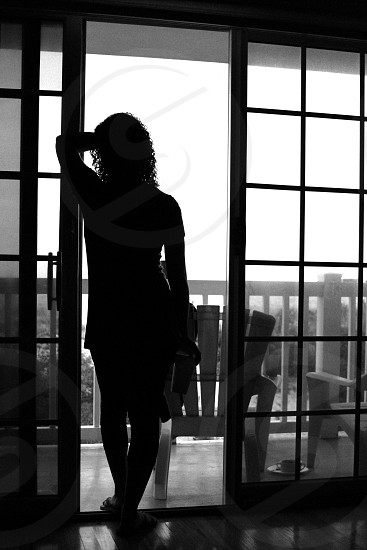 A silhouette of a young woman looking out toward the ocean.  photo