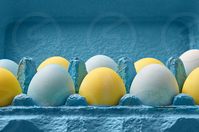 Close-up blue cardboard box with colorful yellow and blue painted Easter eggs presented around blue background with copy space. photo