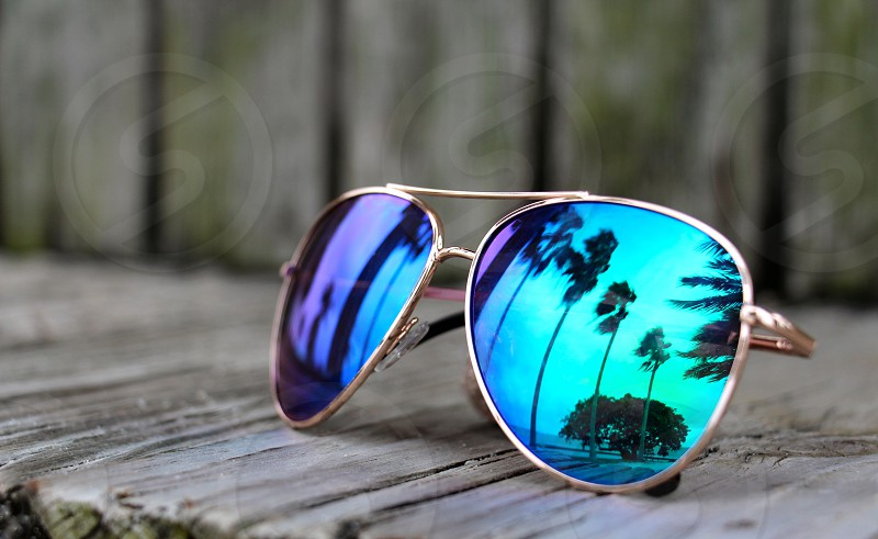 Mirror sunglasses reflecting palm trees and ocean photo