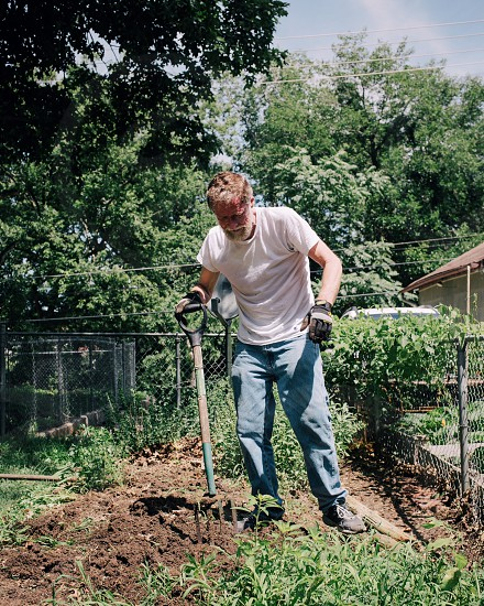 man cultivating soil on the garden photo