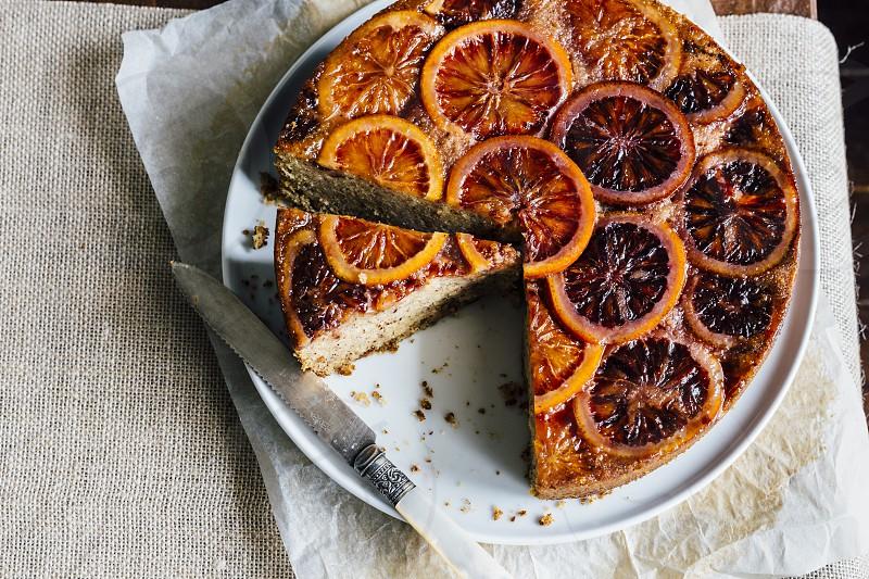 blood orange cake round blood oranges orange oranges overhead round plate knife table food dessert syrup photo