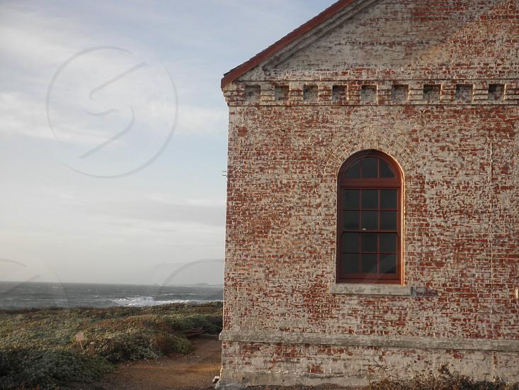 By the sea.  sea ocean seashore building stone building rustic rustic building window photo