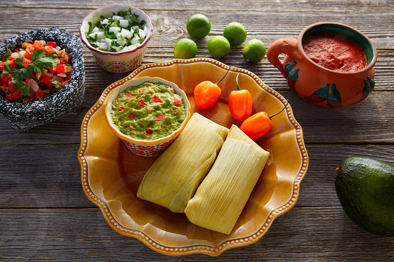 Mexican Tamale tamales of corn leaves with chili and sauces photo
