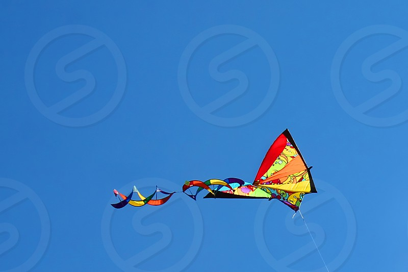 A colorful kite soars against a clear blue sky photo