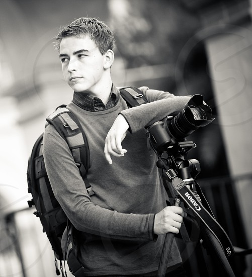 A young professional photographer carrying his camera gear. Tripod lenslens bag backpack. photo