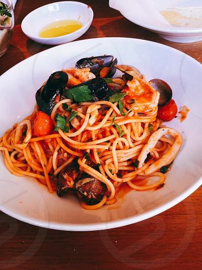 shrimp clams and tomato pasta on white ceramic plate photo
