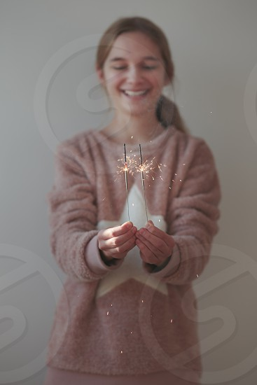 Young smiling girl holding sparklers photo