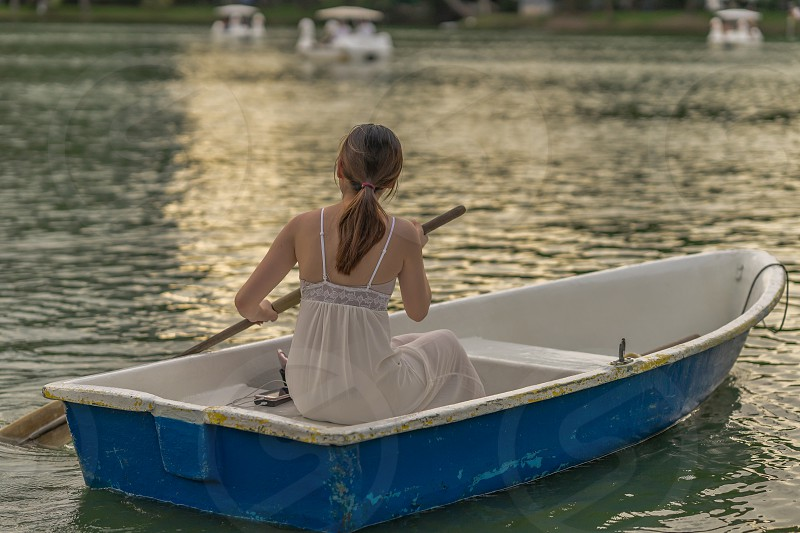 A lady in white in a rowing boat. photo