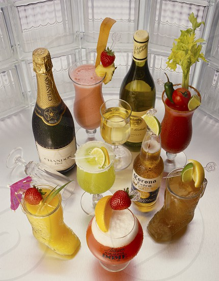 A variety of bar drinks to show the full bar capability of a restaurant club or bistro. Included are Champagne white wine Corona beer Bloody Mary Strawberry-Colada Strawberry Daiquiri Margarita Planters Punch and a Screwdriver.  photo