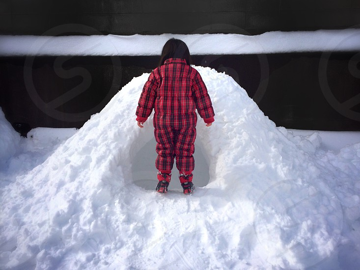 child in red and black plaid jacket standing on snow photo