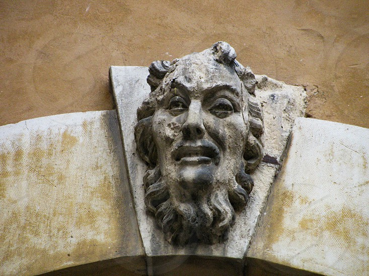 Grotesque carved stone mask or mascaron of a face in the keystone of an arch on the façade of a building in the Palazzo del Capitano in Verona Italy. photo