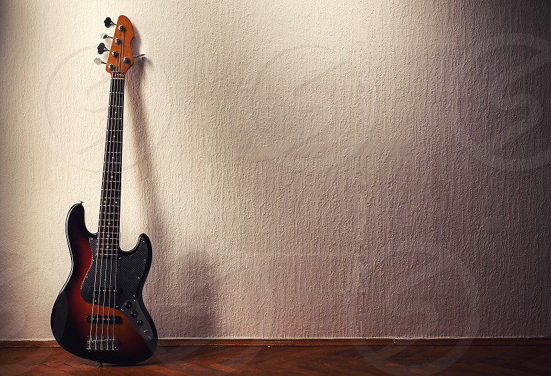 Five string jazz bass leaning to the wall.  photo