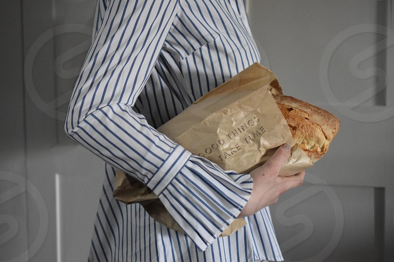 Young woman carrying a fresh loaf of bread. photo
