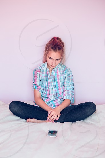 Young girl wearing jeans waiting for message looking at smart phone sitting on bed with legs crossed in room at home photo