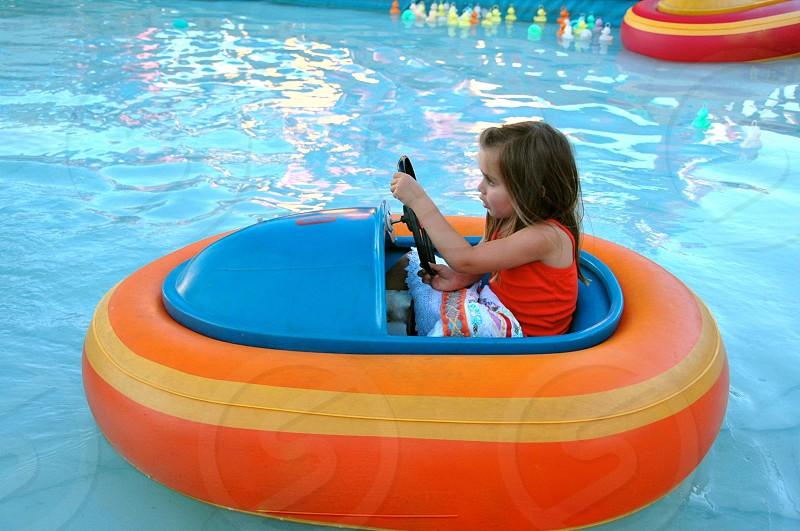 Girl driving orange boat photo