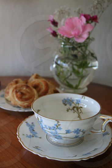 Bedside table with vase of flowers pastries and tea cup photo