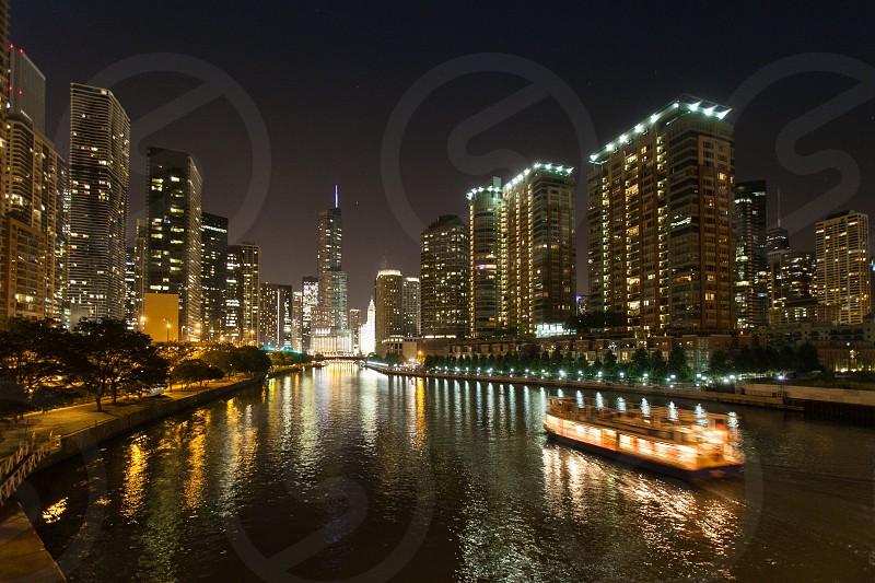 Chicago water taxi on canal at night. Boat buildings trump tower skyscrapers cityscape evening dark boat movement. photo