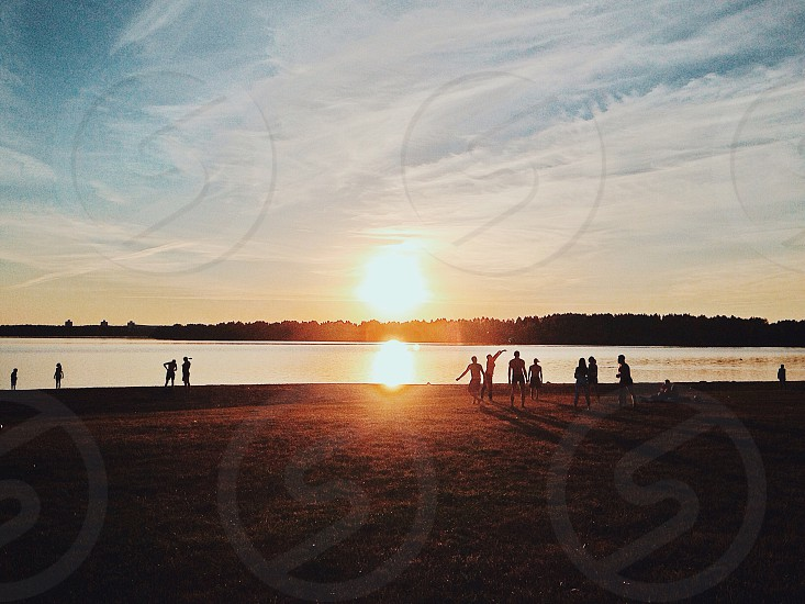 people playing on a lake beach with the sun setting over land in the distance photo