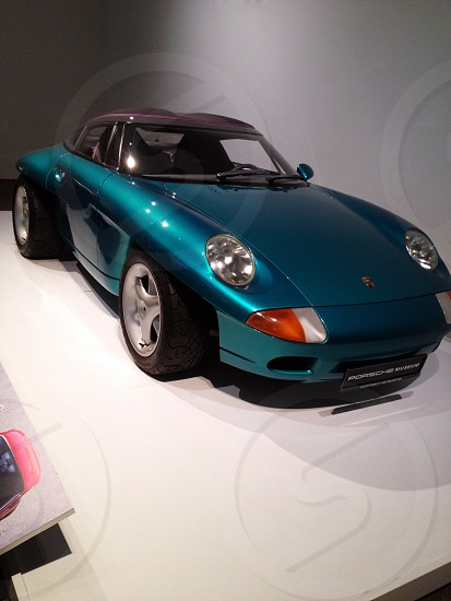 A vintage teal colored Porsche in a museum photo