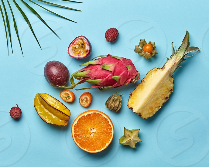 A set of halves of orange pineapple passion fruit and whole carambola pitahaya fruit on a blue background decorated with palm leaf from copy space. Flat lay photo