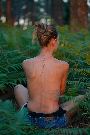 Young woman posing back naked in the forest photo