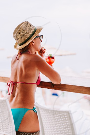 Young woman enjoying cocktail in a beach bar photo