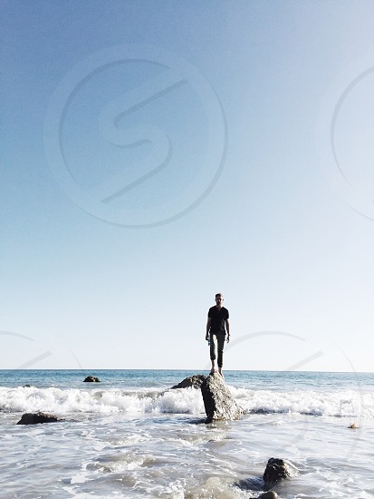 man standing on rock at the shore photo