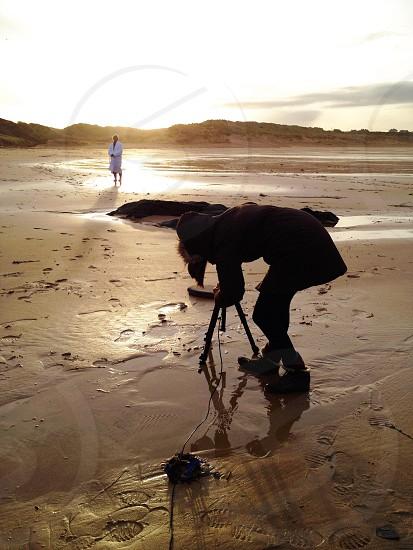 woman putting tripod on brown sand photo