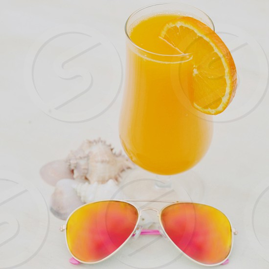 Freshly squeezed orange juice - summer holiday beach shell sunglasses fruit drink photo