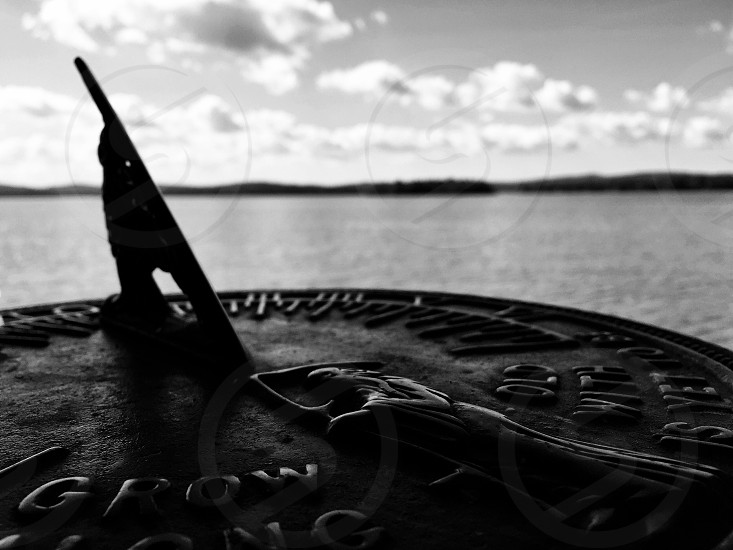sundial in grayscale photo