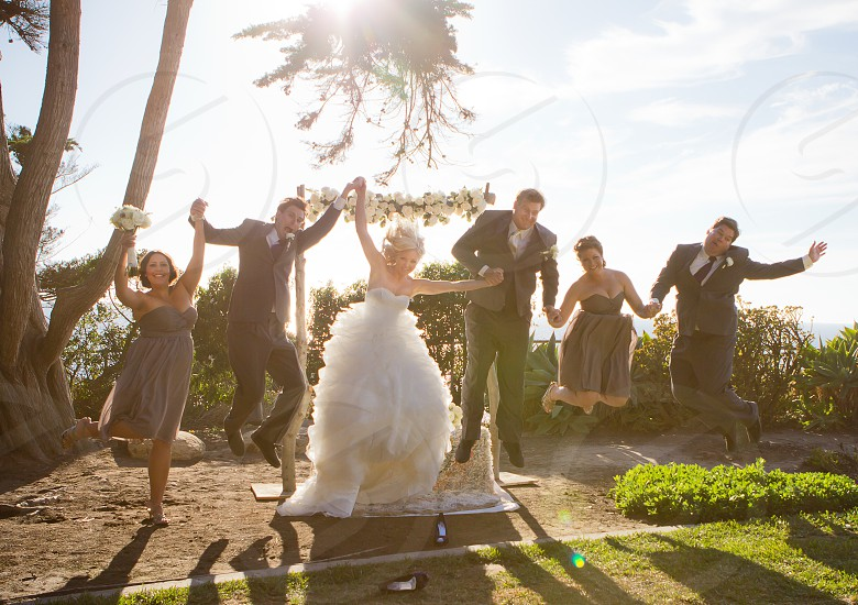 3 women with 3 men doing jump shot while wearing wedding gown and formal suit photo