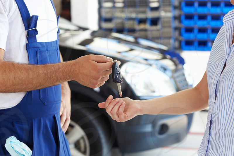mechanic; man; woman; giving; car; key; client; people; male; female; cropped; close-up; unrecognizable person; Caucasian; young; adult; young woman; young man; mid adult; 30s; 20s; standing; side view; human hands; hands; holding; getting; taking; keys; car keys; indoors; garage; repair station; mechanic shop; transportation; transport; vehicle; auto; automobile; passenger car; motor vehicle; broken car; repair; car repair; repairing; occupation; fixed; service; service industry; horizontal photo