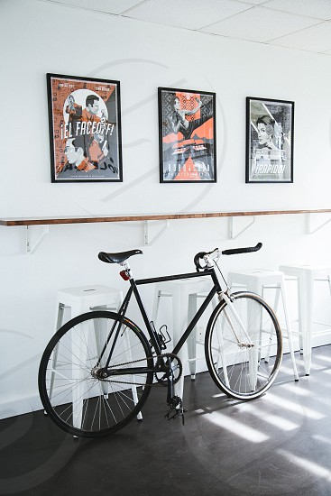 black rigid bike covering four white plastic stool chairs over white and brown wooden shelf over 3 rectangular framed posters mounted on white concrete wall photo