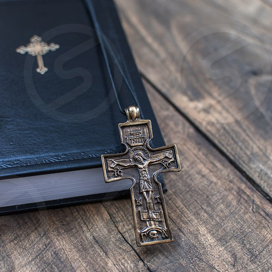 Closeup of  Christian cross necklace next to holy Bible photo
