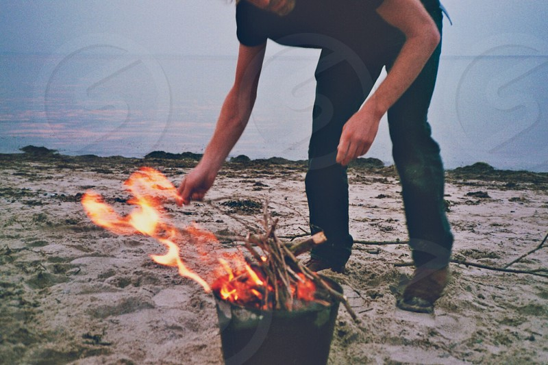 Beach campfire summer adult BBQ fire sea grill wood photo