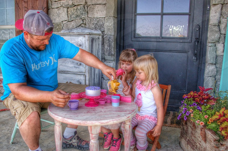 man and girls having a tea party photo