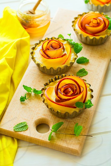 Tartlets with plum roses decorated mint leaves on white wooden background. Selective focus photo
