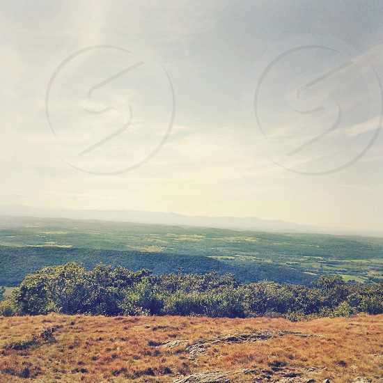 view from the top of a landscape with forest and cloudy sky photo