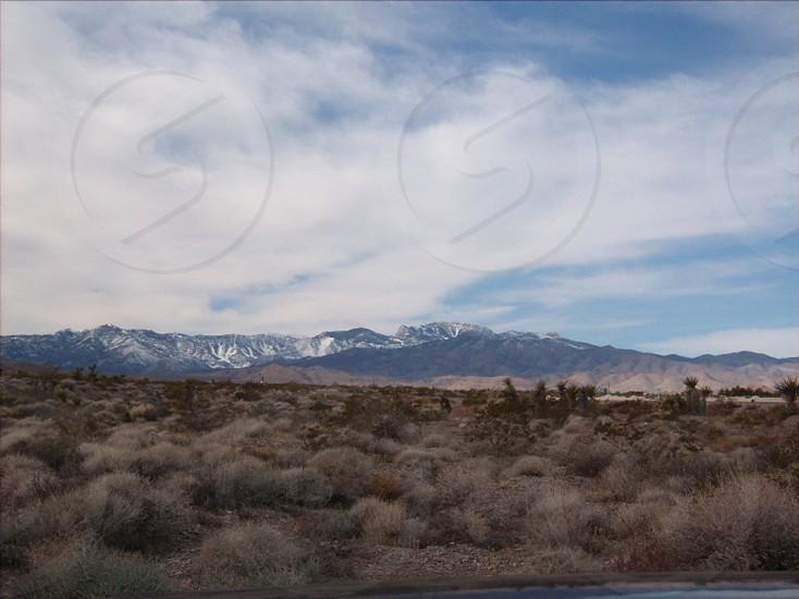 Distant snow capped mountains across desert photo