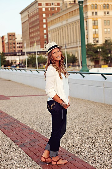 woman in white cardigan and blue denim jeans standing photo