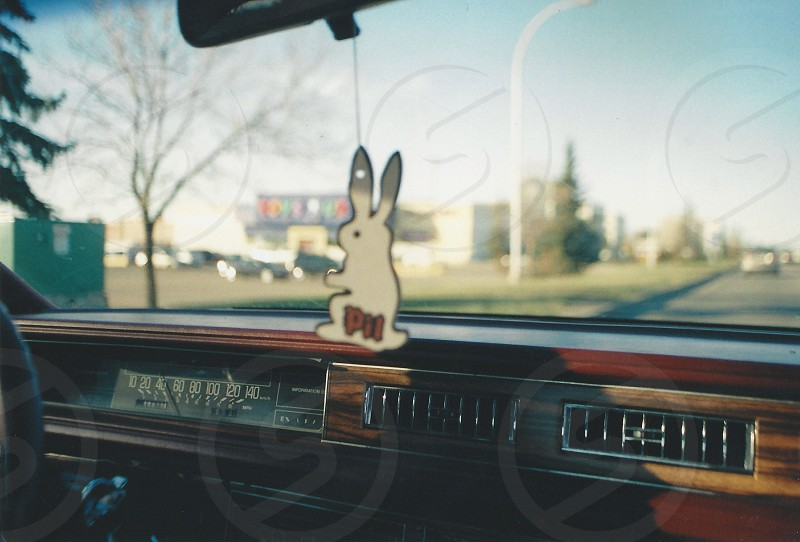 Pilsner car air freshener hanging from the rear view in an 1988 Buick Park Avenue with wood panel and flat spedometer photo