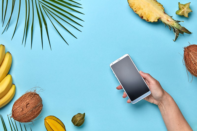 A woman's hand holds a mobile phone against a blue background around a tropical fresh fruit with copy space. The concept of buying online. Flat lay photo
